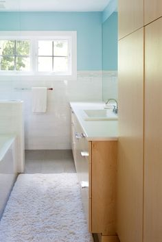 honey colored wood, ice white tile, blue walls, and bright sunlight make this a favorite bathroom design of mine.  Interior design of for this Swarthmore, PA home by www.down2earthdesign.com.