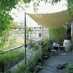 Faire d'un balcon ou d'une terrasse avec un peu de vis à vis une fausse cabane à la campagne : des canisses au fond, une toile tendue, des graminées pour cacher joliment la vue tout en restant mobiles... Ajouter un plancher en bois et de gros galets entre les pots de fleur pour l'ambiance.