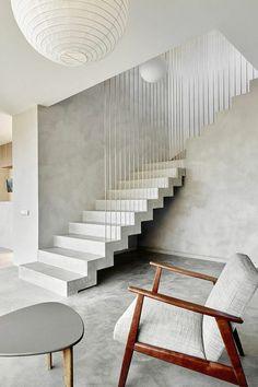 appartement minimaliste, fauteuil en bois et tissu, escalier moderne, murs et sol et béton ciré