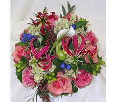 Gloriosa lilies, lady slipper orchids, pink shaded roses with berry accents create a bright and refreshing bouquet. Original Design By Fireside Flowers.