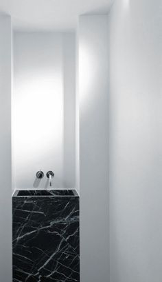 a square black marble sink is a perfect match for a masculine space