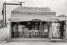 "February 1939. ""Hamburger stand in Harlingen, Texas."" Chili 10 cents, breakfast 25, and the 7up is real."