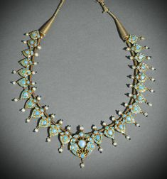 A turquoise-set and enamelled gold necklace, North India, 19th century, comprising twenty-five pendants in the form of stylised blossoms with a central, larger pendant featuring facing birds, each set in the kundan technique with turquoise and mounted seed pearls, the reverse with red, green, blue and white enamel details, golden thread string with tassel terminals, fitted in custom box
