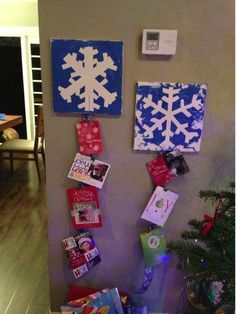 On a blank canvas, create a snowflake  design with masking tape.  Have child paint over it with blue acrylic/canvas paint.  Remove the tape and there you have a beautiful snowflake design. Find some festive ribbon and place on back (I stapled) and hang your Christmas cards with little binder clips.  Joint creation with @thekyla Adams