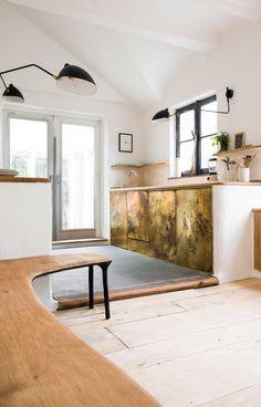 Dans la cuisine, la banquette en chêne au piètement en bois brulé épouse les murs arrondis et passés à la chaux. Chaque centimètre de ce décor a été créé sur mesure des propres mains de l'artiste. Appliques Serge Mouille.