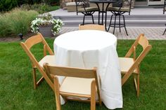 """Perfect seating for a cocktail party or cocktail hour at a wedding.  30"""" Round Table with natural wood folding chairs."""