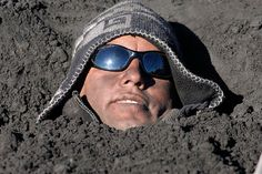 Coronel, Chile: A resident buries himself in an ash deposit during a protestPhotograph: Jose Luis Saavedra/Reuters