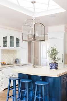 kitchen with painted navy blue island + bar stools, white cabinets, lantern pendant lighting