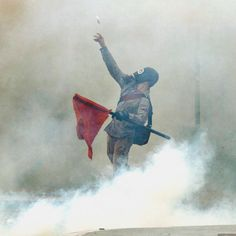 A protester wearing a gas mask and engulfed in clouds of tear gas throws a projectile towards riot police