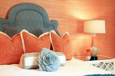 Lucy and Company    Sensational orange & blue girl's bedroom with orange grasscloth wallpaper, teal blue & ivory geometric pattern headboard, orange shams, baby blue flower pillow, orange and turquoise blue Bungalow 5 Cordova Lamp and Worlds Away Ava Nightstand in Marshmallow Lacquer.