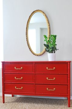 Love the gold hardware with the gold mirror against the bright red.