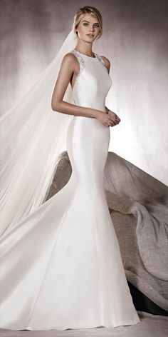 If you love renovated classics, this is your wedding dress. A mermaid wedding dress in mikado that hides an incredible back crafted in a geometric design in gemstones and tulle that makes this dress a unique piece. Doubtlessly a spectacular dress.