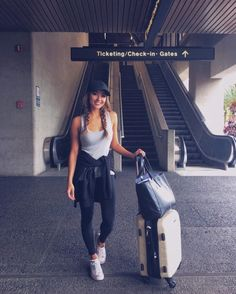 Jessica Ricks wears a simple grey vest with black leggings, a matching black cap, and white Converse sneakers to create this comfortable travel style. Brands not specified.
