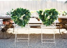 Greenery wreaths on chairs   Check out our blog about wedding wreath inspiration @ JustBeTheBride.com!