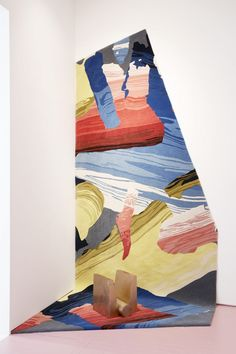 One of Kinder Modern's rugs, patterned with bold colourful graphics, is installed up a wall in the same space.