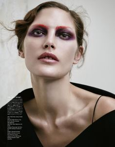 Catherine McNeil wears purple eyeshadow with eyebrows painted red and Dior top