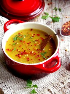 Bhaja Muger Dal ~ roasted mung dal soup 1/2 cup  + 3 tablespoons split yellow mung/moong 2-3 cups water 1/2 teaspoon turmeric salt 1/2- 3/4  teaspoon sugar, or adjust to taste 2-3 fresh green chiles, finely chopped (remove seed if you do not want spicy) 1 tablespoon ghee + some more to drizzle while serving a good pinch of asafoetida/hing 1-2 red dried chili pepper 1/2 teaspoon cumin seeds 2 bay leaves (tej patta) 1.5 teaspoon grated fresh ginger crushed red pepper and fresh cilantro