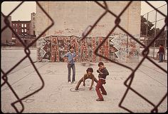 "Three boys and ""A Train"" graffiti in Brooklyn's Lynch Park in New York City. June 1974. Photo by Danny Lyon."