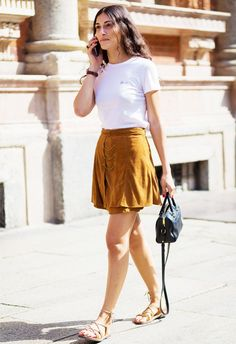 A white t-shirt is worn with a mini skirt, strappy sandals, and a mini Saint Laurent duffle bag