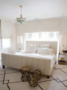 Stunning bedroom centers on an channel tufted bed layered in soft ivory bedding below French doors dressed in side by side ivory roman shades, framed by walls clad in Osborne