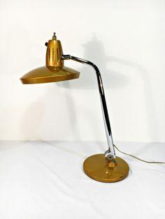 Auténtica lámpara de mesa vintage de los años 60 de la conocida marca española FASE modelo FARO en color dorado. Esta lámpara en concreto, a pesar de pertenecer al modelo FARO, es muy difícil de encontrar ya que el interruptor se encuentra en el lateral de la parte superior de la pantalla y no en …