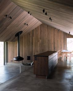 The main cabin features a split-level living space, with a kitchen and dining area that steps down to connect with the lounge area, where a suspended fireplace provides a striking feature.
