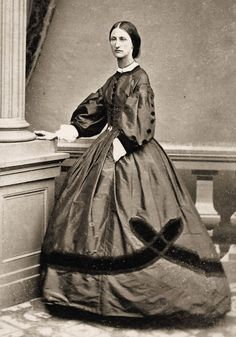 1860's Day Dress with lavish velvet trim, dress probably silk; and her hand is in a pocket.