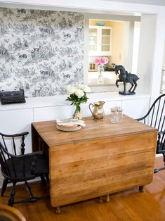 A drop-leaf dining table is a great way to create space in smaller dining areas. Windsor chairs paired with English country wallpaper are elegant touches to this traditional dining room.