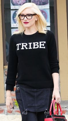 "Gwen Stefani in a ""Tribe"" black sweater, black denim overalls, a red bag, and statement eyeglass frames"