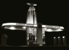 """Night view of one of the Associated Oil Company's spectacular art deco-styled """"Flying 'A' """" gas stations - probably late 1930's."""