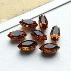 8 vintage amber glass navette stones set into brass pronged settings.  These have flat backs and are perfect for making Miriam Haskell style collage jewellery.  Made in the USA, 1960s.  Each piece measures 9mm x 5mm at the top, and 7mm x 4mm on the base. (3/8 x 3/16 and 1/4 x 3/16)  8 per lot  I ship worldwide from the UK and charge a flat rate shipping of £1.50 in the UK and £3.50 worldwide, meaning no matter how large your order, the shipping cost stays the same.