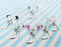 High Heel Shoe Wine Glass Charms – Set of 6 This stylish wine charm set is perfect for your bachelorette party, fashion theme birthday accessory or even to give as favors to guests. Each silver plated brass ring holder a gorgeous mix of different color of glass crystal beads black, white, deep pink, light green, teal and blush pink, silver plated rhinestone rondelles and silver plated metal beads. The high fashion themed charms are made of a silver-color tone and feature stiletto high heel…