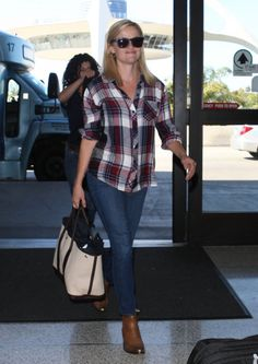 Reese Witherspoon in a plaid shirt and tan boots