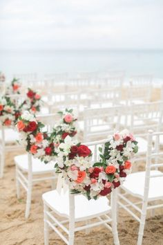 Loving the floral accents on these beach wedding chairs.