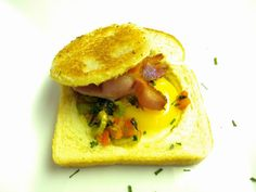 My kids love this as a meal.  Simply grab a large cookie cutter to fit in the diameter of a slice of bread (or bread bun), fill it with an egg, bacon and herbs and cook it on a flat pan. Top with the cut out piece of toast!  Delish.
