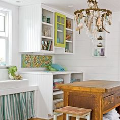 This hardworking mudroom may sport a sink and an island workstation, but it's still a just-right setting for a seaside-glam touch, such as the all-natural oyster-shell chandelier shedding light on the scene.