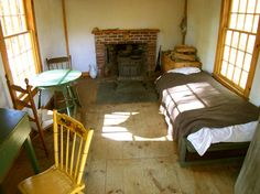 Henry David Thoreau's 10'x15' home, furnished with only the necessary basics: a bed, a table, a desk, and three chairs.