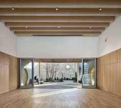 MUMA Architects add playful touches like porthole windows, a soaring spiral staircase and waterfall gutters to a community centre in Cambridge, England. Cambridge, Reception Desk Design, Timber Buildings, Youth Center, Timber Structure, Cedar Shingles, Oak Panels, Ceiling Windows, Ceilings