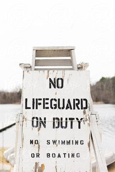 """No lifeguard on Duty"" sign attached to a lifeguard stand at a lake by Amanda Worrall - Stocksy United - Royalty-Free Stock Photos"