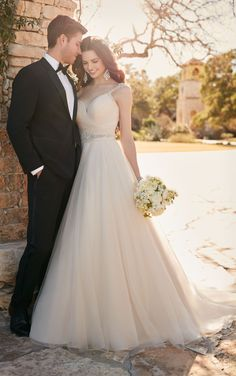This tulle and Regency organza A-line wedding gown from Essense of Australia boasts hand-sewn Diamante beading on its shoulder straps, back trim and waistline. The sweetheart bodice and thick waist belt are ruched to flatter. The back zips up under fabric-covered buttons.