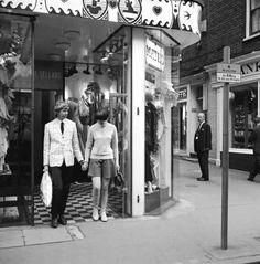 14 October 1966: A young couple coming out of Mates boutique, which sells both men's and women's clothing. | 14 Marvellous Photos Of Carnaby Street In The '60s