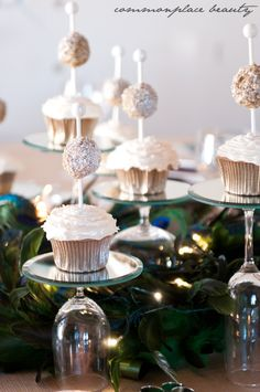 upside down wine glasses, topped with a small round mirror for an individual cupcake stand!  Plus the cupcakes are adorable