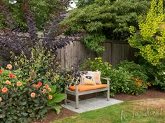 A purple and chartreuse smoke bush flank this bench in the lovely garden of Carol Ager, Woodinville WA