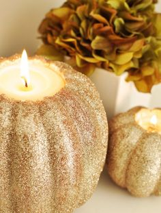 DIY Foam white pumpkins covered in glitter are hollowed to hold candles.