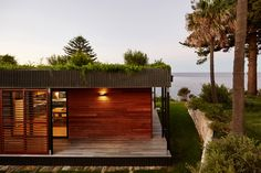 ArchiBlox gave this prefabricated beachfront house near Sydney a verdant plant-covered roof to help it blend into its clifftop setting.
