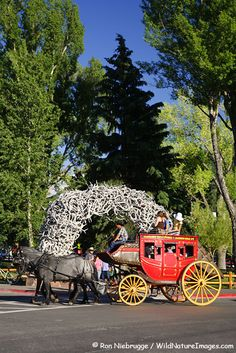 A stagecoach passes by the elk antler arch in downtown Jackson Hole, Wyoming