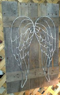 Metal angel wings on pallet wood