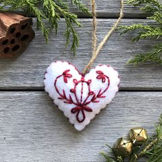 Hand-Embroidered, White Heart-Shaped Ornament • Made of 100% Acrylic Felt • Stuffed with Poly Fil • 3.25 across from widest point on the ornament • 3 tall • 1 thick • Natural, Jute Chord Each piece has unique variations as they are hand-made.