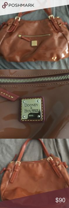 Dooney & Bourke handbag patent leather Really nice well taken care of Dooney and Bourke bag in a peanut butter brown patent leather that's just to die for!  I'm just sitting out my closet I haven't use this bag in a really long time and I don't see one thing wrong with it. Side tassels front zip pocket red cotton lining interior with brown leather trim clip for your keys for interior pockets no shoulder strap. Bags Shoulder Bags