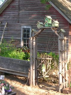 Adorable rustic birdhouse arbor- I also like that they used a bench as a border.